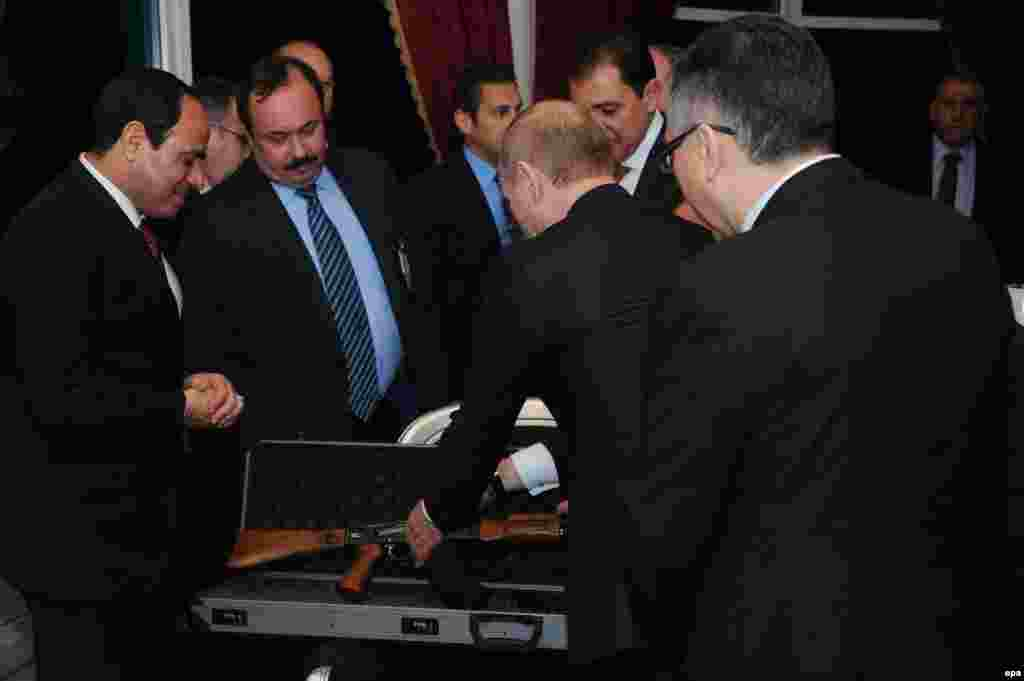 Egyptian President Abdel Fattah Al-Sisi (left) receives a Kalashnikov rifle as a gift from Russian President Vladimir Putin (second right) in Cairo on February 9. (epa)