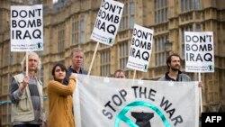 Участники пикета протеста против авиаударов по Ираку перед зданием парламента Великобритании в Лондоне