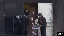 Полицейские эвакуируют жителей в районе Порт-де-Винсенн. Париж, 9 января 2015 года.
