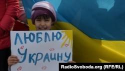 Ребенок с плакатом во время акции крымских татар за мир и против нахождения российских военных в Крыму.