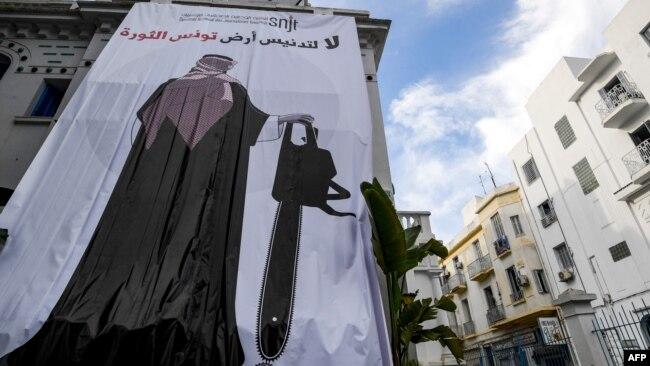 روزنامهنگاران تونسی بنری بر سر در اتحادیه خود نصب کردهاند که ولیعهد عربستان را با یک اره نشان میدهد؛ اشاره ای به قطعهقطعه شدن جمال خاشقجی.