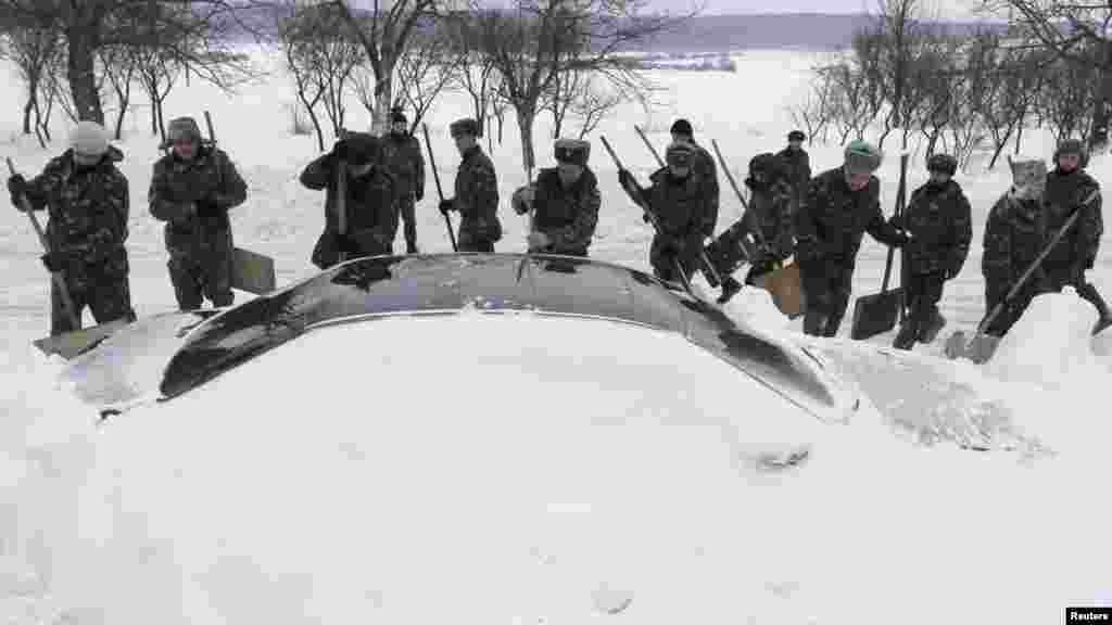 In Ukraine, emergency workers attempt to free a car trapped in snow after a blizzard struck the western city of Brody.
