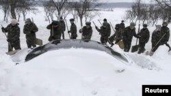 Сотрудники ЧС расчищают машину, заваленную снегом. Броды, 17 декабря 2012 года.