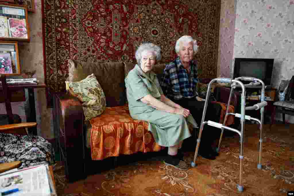 Anatoliy and Ludmila sit on a sofa in their house located at the front line near the destroyed international airport in Donetsk, Ukraine. According to the volunteer organization Donbas Development Center, there are about 1,500 elderly people and people with disabilities in the Donbas region who are in need of assistance because they cannot take care of themselves. (epa/Alexander Ermochenko)