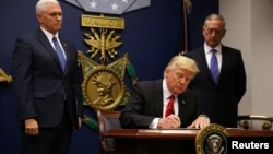 U.S. President Donald Trump signs his first executive order on immigration on January 27.