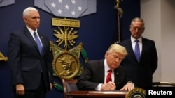 U.S. President Donald Trump signing his first executive order on travel on January 27.