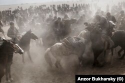 Horsemen rush for the headless goat during a game of buzkashi near Bukhara in 2014.