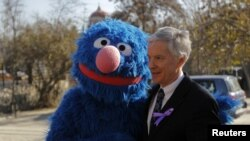 "U.S. Ambassador to Afghanistan Ryan Crocker poses for pictures with ""Sesame Street"" character Grover before the inauguration of a show in Kabul on November 30."