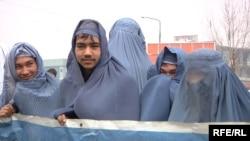 Афганские активисты в парандже проводят акцию на улице, пытаясь привлечь внимание общественности к проблеме нарушения прав женщин. Кабул, 5 марта 2015 года.