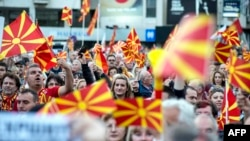 Protesters in Skopje wave flags during one of several demonstrations this year against a law making Albanian the second official language of Macedonia.