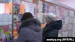Покупатели в аптеке в Казахстане. Надпись на стекле гласит: «Масок нет».