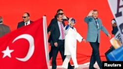 Turkish Prime Minister Recep Tayyip Erdogan and his wife, Emine, wave to supporters as they arrive at a rally in Istanbul on June 16.