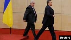 Свергнутый президент Украины Виктор Янукович (справа) покидает пресс-конференцию в Ростове-на-Дону. 28 февраля 2014 года.