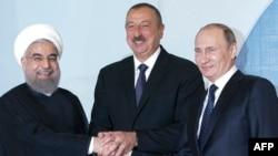 Russian President Vladimir Putin (R), Iranian President Hassan Rohani (L) and Azerbaijani President Ilham Aliyev pose for a photogrpah during their meeting in Baku, August 8, 2016