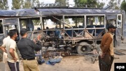 Pakistani security officials inspect the site of a suicide bomb blast that targeted a police bus in Karachi on February 13, 2014.