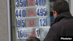 A man and child look at the exchange rate in Yerevan as the Armenian dram lost some 30 percent of its value in one day