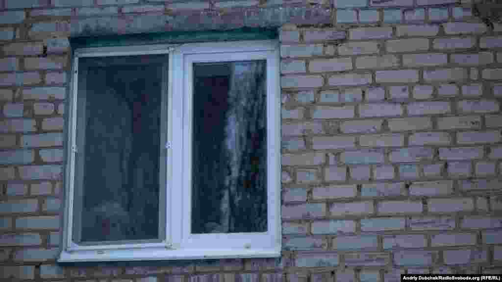 Літня жінка споглядає за вертепом з вікна своєї квартири