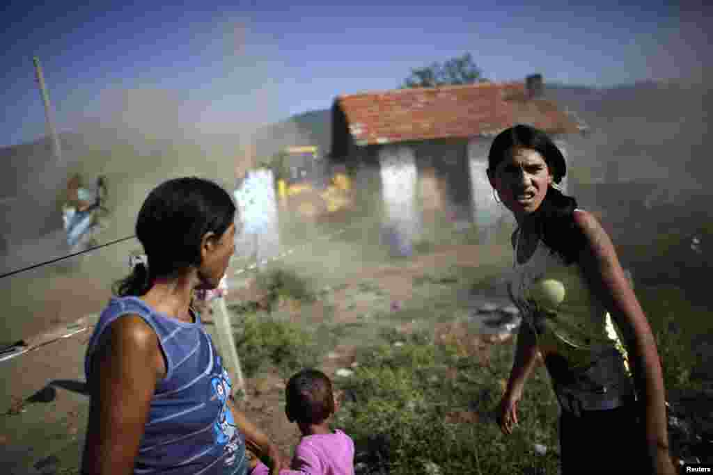 Bulgarian Roma women react as a bulldozer tears down their home in a Roma suburb in the town of Maglizh, some 260 kilometers east of Sofia on September 25. The municipal authorites had ordered the demolishment of some 30 illegally built houses in the area. (REUTERS/Stoyan Nenov)