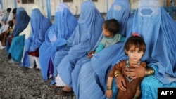 Afghan women and their children are pictured at a UNHCR registration center on the outskirts of Peshawar, Pakistan, in June.