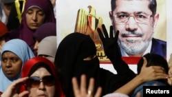 «Мұсылман бауырлар» қозғалысын қолдаушылар Мұхаммед Мурсидің суретін ұстап тұр. Каир маңы, Египет, 1 қараша 2013 жыл.
