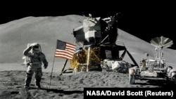 """Астронавт Джеймс Ирвин, пилот лунного модуля, салютует перед американским флагом во время миссии """"Аполлона-15"""" - высадки на Хэдли-Апеннины на Луне 1 августа 1971"""
