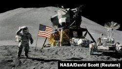 Astronaut James Irwin gives a military salute while standing beside the U.S. flag during Apollo 15 lunar surface extravehicular activity at the Hadley-Apennine landing site on the moon in August 1971.