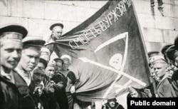Моряки Кронштадта во время революции 1917 года позируют с флагом с клятвой «Смерть буржуям».