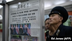 Люди читают газету с фото северокорейского лидера Ким Чен Ына и президента США Дональда Трампа. Июнь 2018 года.