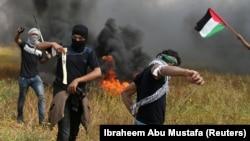 Palestinieni provocînd trupele israeliene la frontiera cu Gaza