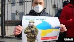Плакат із зображенням президента Росії Володимира Путіна під час акції «Крим – це Україна» біля російського посольства в Києві, 16 березня 2020 року