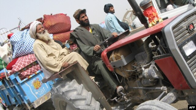 Displaced families fleeing their village in Marjah arrive in Lashkar Gah in Helmand Province on February 8.