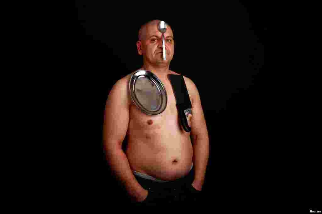 Nermin Halilagic, 38, poses in Bihac, Bosnia-Herzegovina. Halilagic discovered earlier this year that he had the unusual ability to attach items to his body using what he says is a special energy radiating from his body. Without making any special preparations, he says he is able to hold on to spoons, forks, knives, and other kitchen appliances, as well as nonmetal objects like remote controls, plastic items, and cell phones. (Reuters/Dado Ruvic)