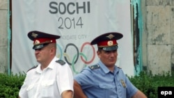 Russia -- Russian policemen in front of a banner promoting the 2014 Sochi Olympic games - 03jul2007
