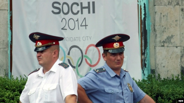Russian policemen stand in front of a banner promoting Sochi during bidding to host the 2014 Winter Olympics.