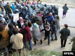 Полицейские силой прорвали кордон женщин, преградивших им путь в поселок Шанырак близ Алматы. 14 июля 2006 года.