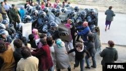 Полицейлер жолдарын бөгеген әйелдер шебін бұзып өтті. Алматы, Шаңырақ ауылы, 14 шілде 2006 жыл.