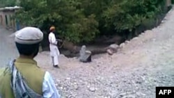 A video grab shows a man pointing an AK47 rifle at a woman identified as 22-year-old Najiba, who is sitting near a ditch shortly before being executed by gunfire in Qol village, Parwan Province.