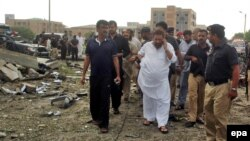 Senior police officer Aslam Chaudhry (in white), inspects the scene of a suicide car-bomb blast targeting his residence in Karachi in September 2011.