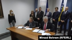Political leaders Bakir Izetbegovic (left) and Dragan Covic sign the agreement in Mostar on June 17.