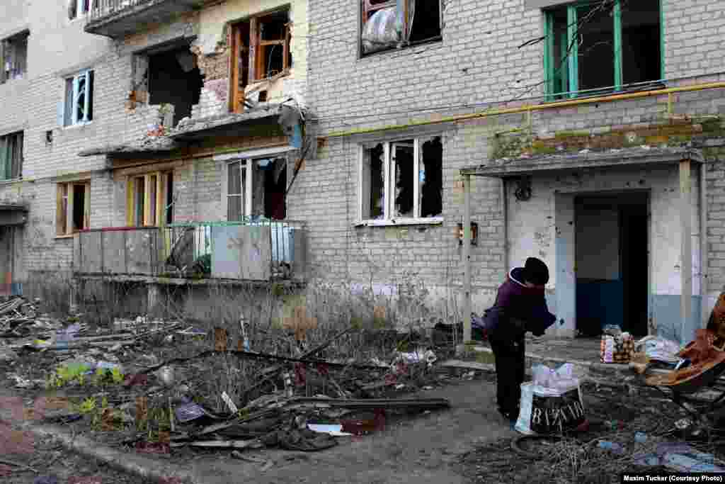 A woman collects possessions from an abandoned apartment block half destroyed by artillery fire in Pisky. April 3, 2016