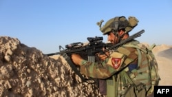 An Afghan soldier takes position during a military operation in Helmand province on August 12.
