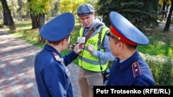Полицейские проверяют документы у журналиста, прибывшего к месту анонсированной протестной акции. 26 октября 2019 года.