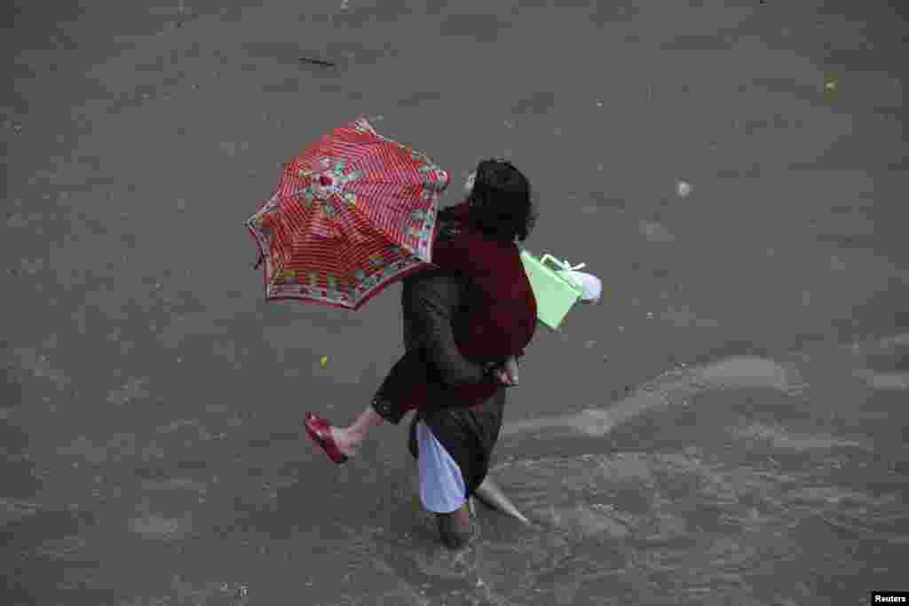 A man carries his daughter as he wades through a flooded road after heavy rains in Lahore.