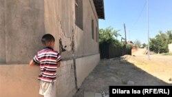 Мальчик у поврежденного в результате взрывов боеприпасов дома в Арыси.