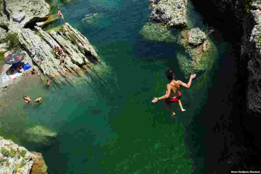 A boy jumps into the Cijevna River to cool off near Tuzi as a heatwave hit Montenegro. (Reuters/Stevo Vasiljevic)