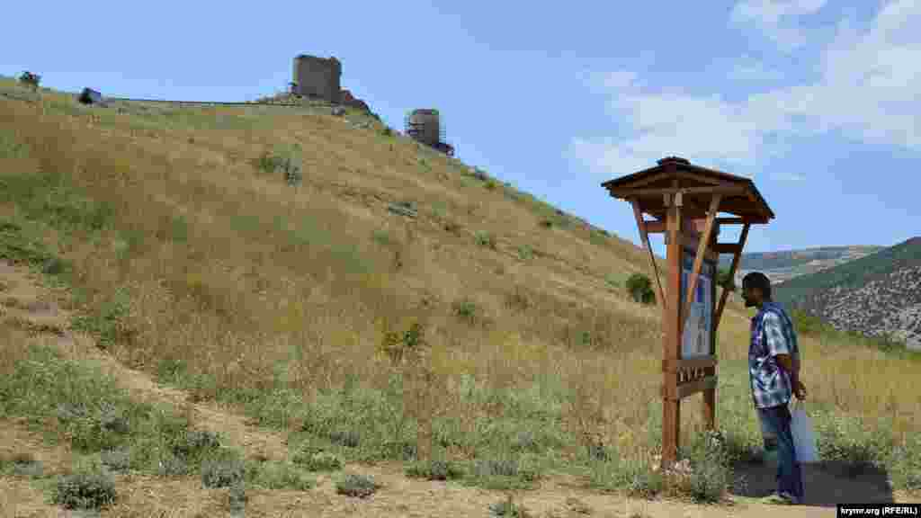 Турист изучает информационный стенд Большой Севастопольской тропы. На холме – развалины генуэзской крепости Чембало. Отсюда начинается и наш путь