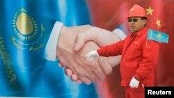 «Түркіменстан-Қытай» газ құбырының Қазақстан арқылы өтетін бөлігінің ашылу рәсімінде үлкен постердің жанында тұрған қытай жұмысшысы. Отар қаласы маңы, Жамбыл облысы. 12 желтоқсан 2009 жыл.