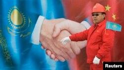 Китайский рабочий стоит перед плакатом во время церемонии открытия казахстанского участка нового трубопровода Туркменистан — Китай протяженностью 1 833 километра на станции Отар. 12 декабря 2009 года