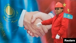 Қытай жұмысшысы Қытайға тартылған газ құбыры баннерінің жанында тұр. Қазақстан, Отар, 12 желтоқсан 2009 жыл. (Көрнекі сурет)