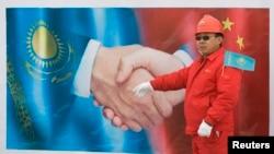 Китайский рабочий позирует на фоне постера на церемонии открытия казахстанского участка газопровода Туркменистан — Китай в районе города Отар Жамбылской области. 12 декабря 2009 года.